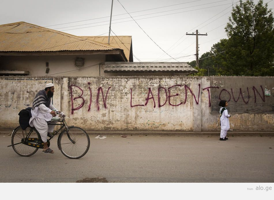 "Residents of Bilal Town pass recently spray-painted graffiti reading ""bin Laden Town."""